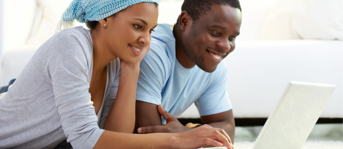 Young black couple lying on floor looking at laptop